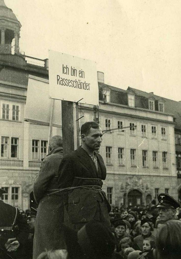 "Eisenach, 15 November 1940. Polish forced laborer Eduard P. with poster ""I am a race defiler"". Source: Stadtarchiv Eisenach"