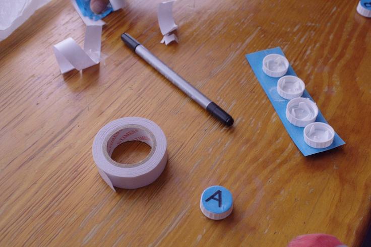 Recortamos el contorno del tapón y escribimos una letra en el centro. También podemos escribir la tira de tapones completa y hacer el siguiente paso todo de una vez.