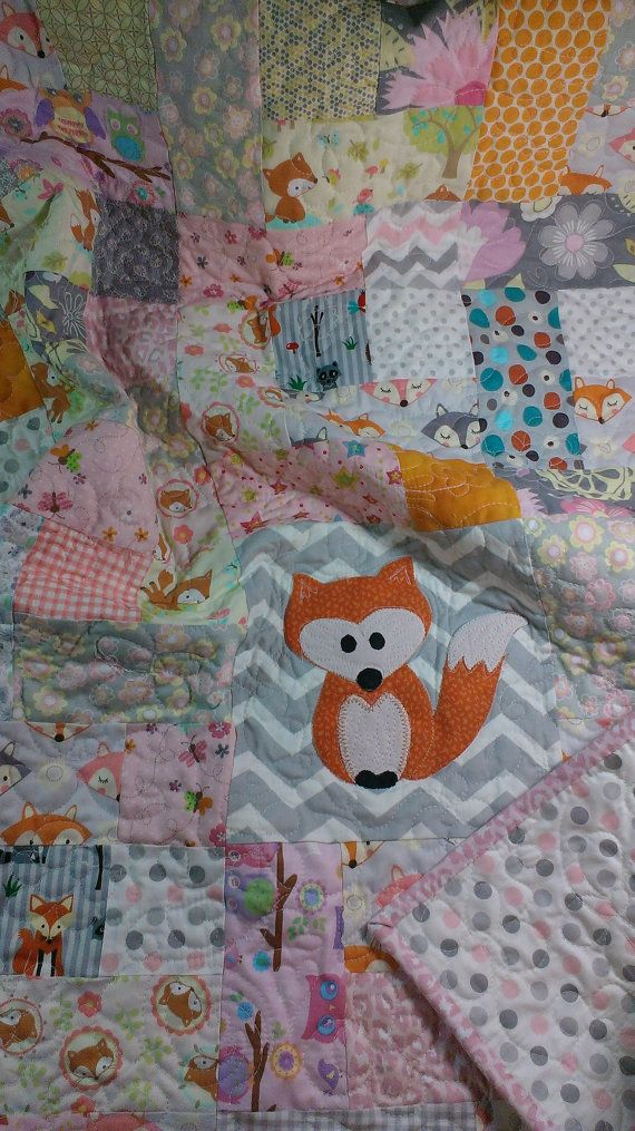 This pink and gray quilt is loaded with little fox prints. The muted colors are primarily gray, pink and a little pale yellow with an orange fox.