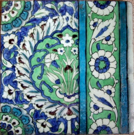 DAMASCUS TILE . . . . . . . . . . . . . . . . . . . . . . . . . . . . . Syria, 17th century 26 x 26cm A square stone paste tile painted in underglaze shades of cobalt blue, apple green and turquoise. A central cartouche surrounded by white serrated leaves, contains a symmetrical floral arrangement against an apple green ground on a cobalt floral ground, rosettes at the two corners,to the right turquoise guard stripes delineate a scrolling design of intertwined leaves and rosettes.