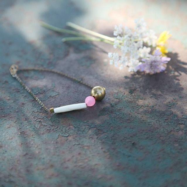 """Un bracelet délicat et moderne composé d'une perle en laiton, d'une perle rose vintage et d'une perle en os d'Afrique. La chaîne en laiton, solide et discrète, complète l'aspect authentique de ce bijoux.Pourquoi on aime :Originalité et finesse pour un rendu du plus bel effet sur votre poignet.Notre avis sur le créateur : Laeti Grena nous surprend avec sa nouvelle collection """"Eté Indien"""", actuelle et colorée."""