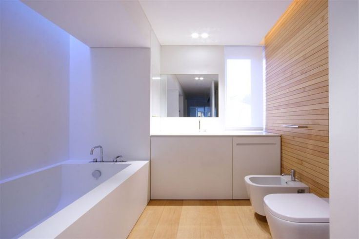Ultra-modern minimalist bathroom contrasts pure white amenities, including vanity and soaking tub, with natural wood panel wall and flooring.