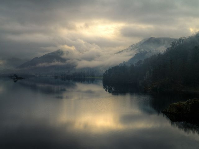 The cloud, as if fallen from its place in the sky, reveals a glimpse of light, the still waters of Ullswater double the light in the scene. This was shot in The Lake District, UK, 12-21-2012.