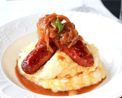 Bangers and mash - sausage on a bed of mashed potatoes and served with rich onion gravy
