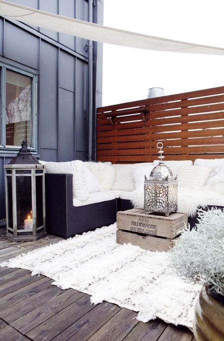 what a fantastic idea for a winter porch... faux fur rug and hurricane vase in winter white