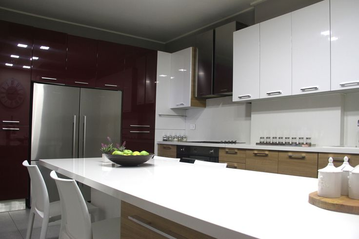 Glossy rich red cabinets wall houses the refrigerator adding spirit to this airy kitchen designed by decoaid