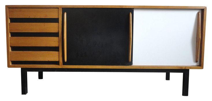 """Enfilade modèle """"Cansado"""" par Charlotte PERRIAND datant des années 60. Placage de frêne, 2 portes coulissantes, l'une en Formica blanc, l'autre noire, 4 tiroirs, pieds en métal laqués noir. Éditeur : Steph Simon vers 1960. Provenance : cité pétrolière de Cansado, Mauritanie. Multiples restaurations."""