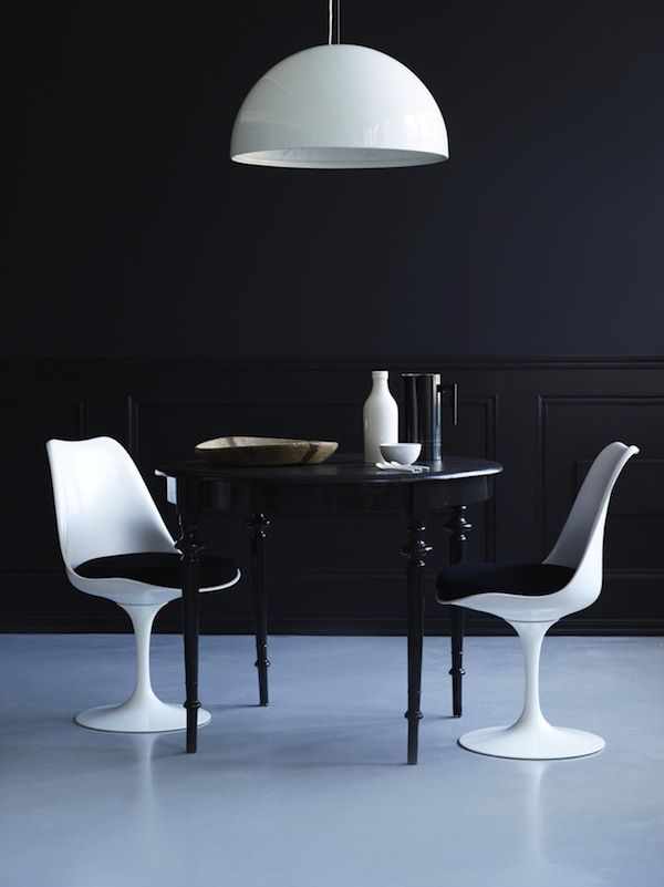 dark timber round table with turned legs with white Tulip chairs, capped off with a Panton lampshade.