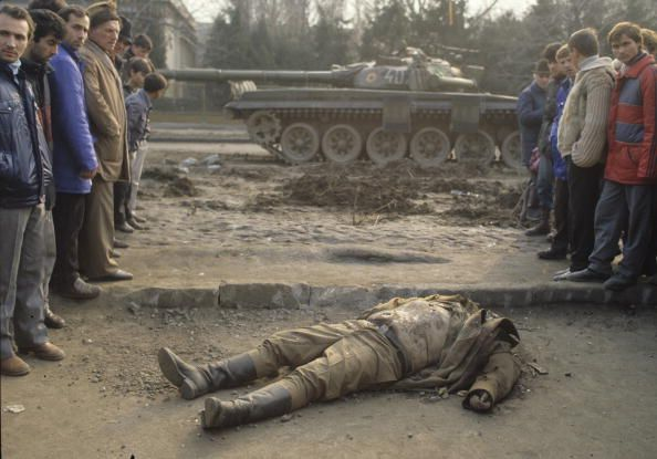 Caption:A dead member of Ceausescu's security team lies in front of a tank in Bucharest during the Romanian Revolution, December 1989. (Photo by Romano Cagnoni/Getty Images)