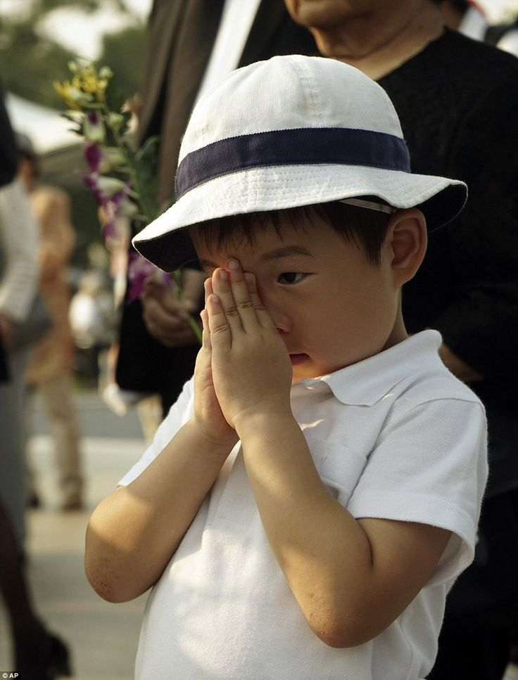 A young boy clasps his hands in prayer at the site of the Hiroshima bomb blast this morning