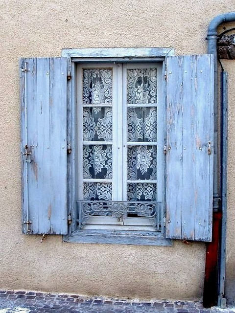 Aged pale blue shutters frame a charming window with lace curtains