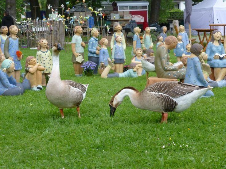 goose between figures of German de Juana,Gänse zwischen Figuren von German de Juana am Diessener Toepfermarkt