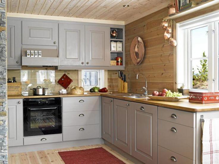 GRÅ HARMONI: Kjøkkenet har fått en delikat fargepalett i grått og beige med røde innslag. Den lange kjøkkenbenken gir god plass til matlaging.