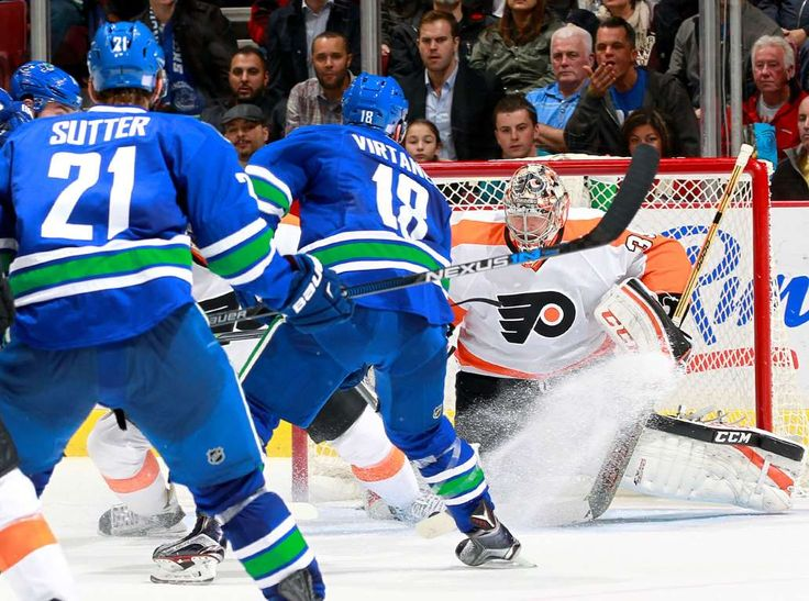 Virtanen arrives on the scene: Brandon Sutter watches as Jake Virtanen of the Vancouver Canucks scores his first NHL goal against Steve Mason of the Philadelphia Flyers during the game at Rogers Arena Nov. 2 in Vancouver, British Columbia, Canada. Vancouver won 4-1. - © Jeff Vinnick/NHLI/Getty Images