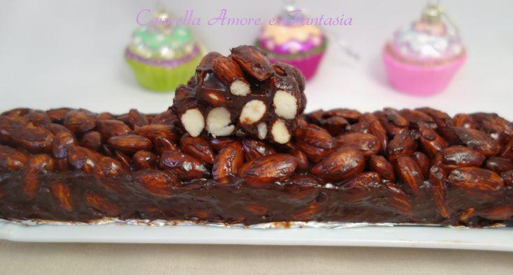 Il torrone di mandorle al cioccolato è un croccantissimo torrone con le mandorle pralinate e la cremosità della ganache al cioccolato fondente e la cannella