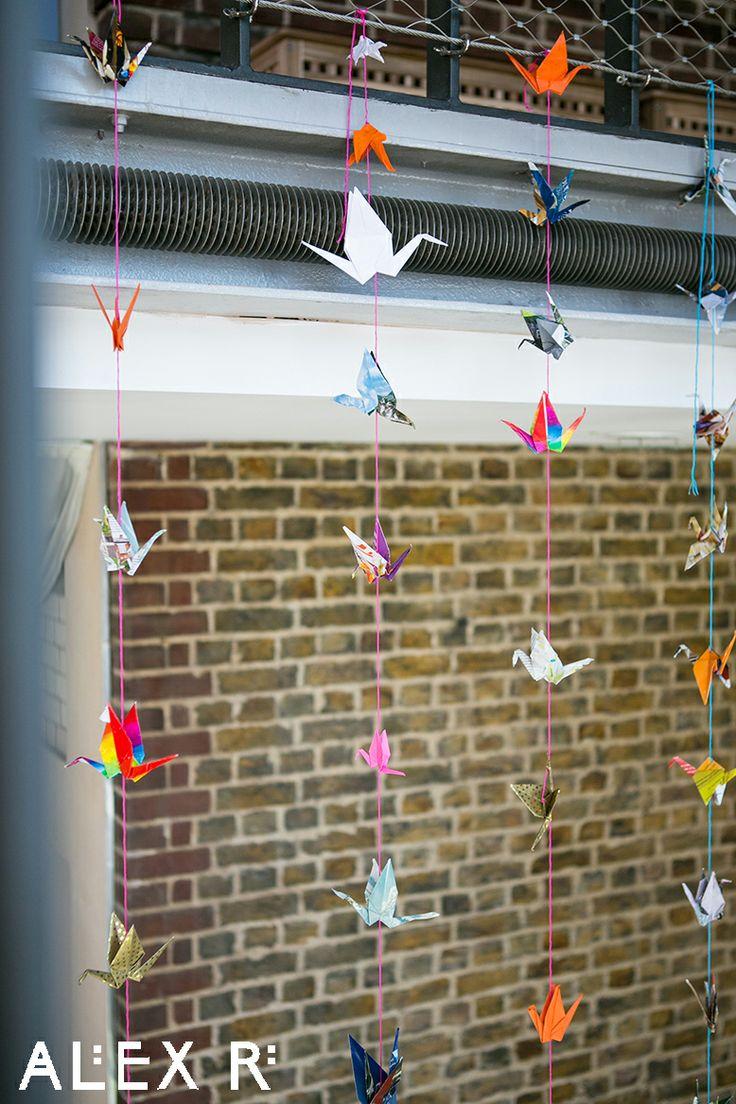 Colourful wedding: paper cranes against a brick wall