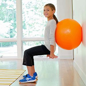 """""""One of the most important functional movements is the squat,"""" says NYC-based kids' fitness expert Steve Ettinger """"and by incorporating an exercise ball into the action, kids will be able to work through the proper range of motion with a supported back."""" Have your child place the ball between her lower back and a wall, then slowly squat until her knees are at 90 degrees. Keeping her core muscles tight, she should then push back to an upright position. Work up to three sets of ten…"""