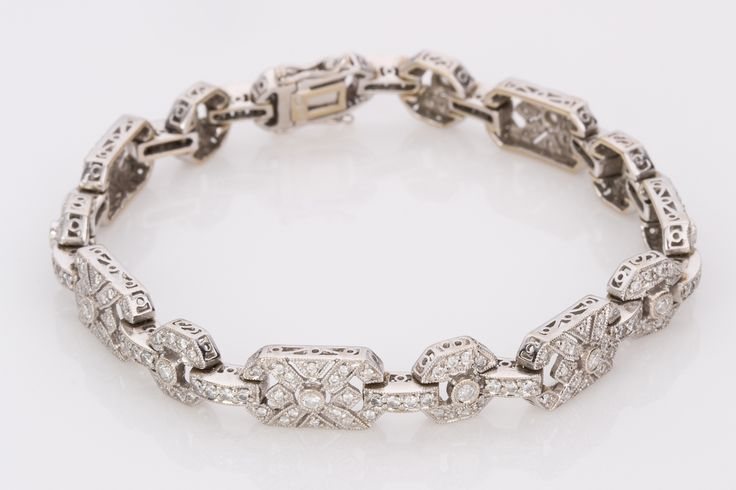 A finely crafted Vintage style reproduction bracelet with loads of diamonds and detail. Made in 18k white gold this Art Deco style bracelet is 7.5mm wide (at its widest point) of alternating large and small link designs each connected with 14 parallel interconnecting links. A total of 238 diamonds makes up this gorgeous bracelet with a total weight of 1.85cts.
