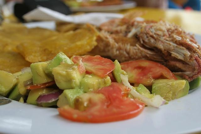 Pargo rojo acompañado de ensalda de aguacate, tomate, cebolla morada, limon, y patacones, via Flickr.