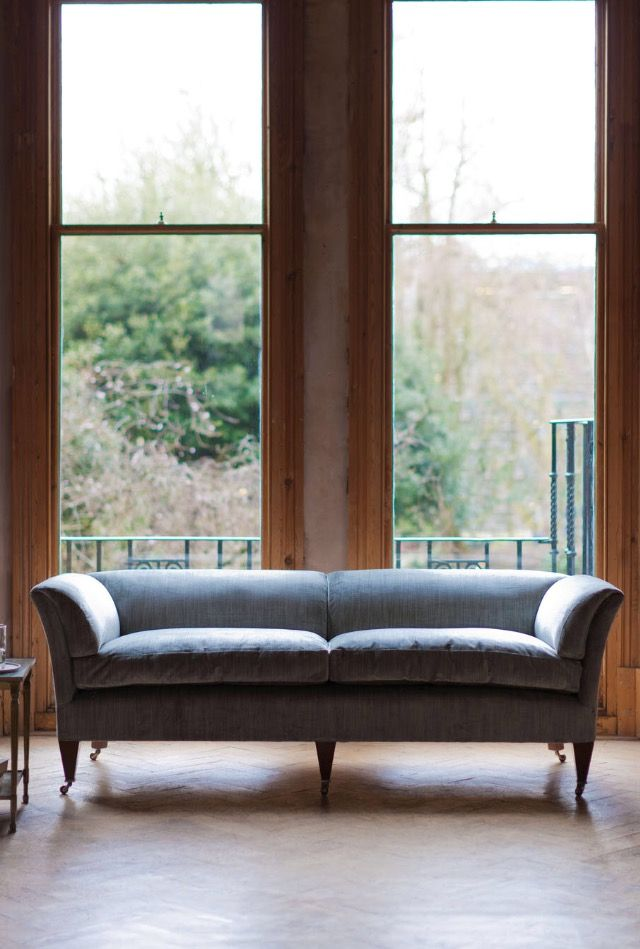 The Pompadour sofa is a signature Beaumont & Fletcher piece. Inspired by an early 19th century neoclassical design, its clean, unfussy lines work just as well in a modern living space as in a traditional drawing room. The deep cushioning of the sofa provides supreme comfort and style. The Low Back Sofa in Como Silk Velvet, Sage (blue) is shown in this image.