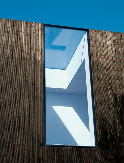 Lluernari unit a la carpinteria de façana d'Arquitectura minimalista. Blanc i fusta.