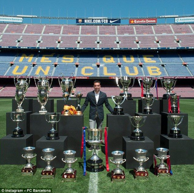 Xavi poses for a photo on the Nou Camp pitch alongside every trophy he won in 17 years at the club, June 2015