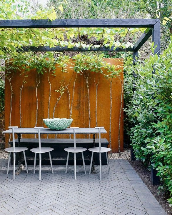 Cool dove grey paving and seats, black table and pergola highlight lively greenery.