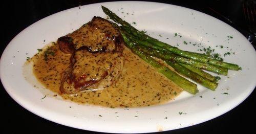 Beef tenderloin, cooked medium rare,  with roasted garlic, thyme, basil and oregano  in a cream sauce. Served with asparagus. S...