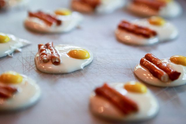 Mini bacon and eggs tutorial- Melted white chocolate chips, yellow M&Ms, and pretzel sticks!