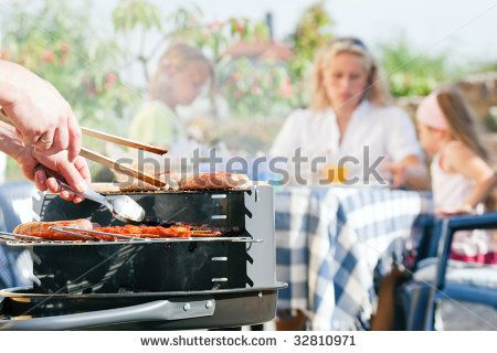 Family having a barbecue in the garden - focus on cooking in the foreground - stock photo