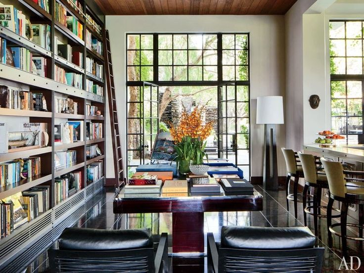The main library is appointed with Minotti armchairs (in the foreground), a custom-made Jean de Merry table, and bookshelves designed by Heller | archdigest.com
