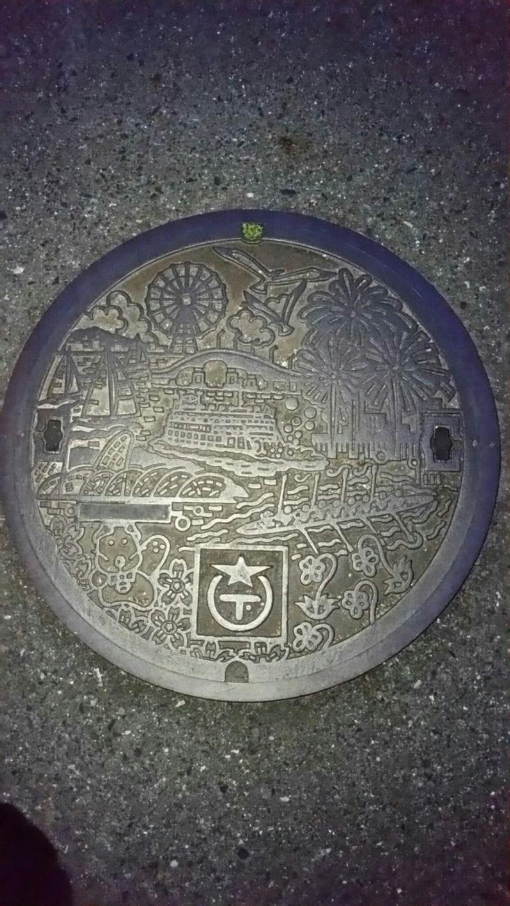 <滋賀県大津市> 市制施行から100年目の大津市の景観をモチーフにした、琵琶湖、琵琶湖大橋、ミシガン船、ヨット、観覧車、 市の鳥・ユリカモメ、市の花・エイザンスミレ、市の木・ヤマザクラ、 花火大会、レガッタ、びわ湖花噴水、犬などと市章に下水の「下」を組み合わせたマークが描かれている。  平成10年10月1日に市制施行100周年を迎え、その記念に蓋のデザインを公募し、 最優秀賞に選ばれた作品が元になったデザイン。