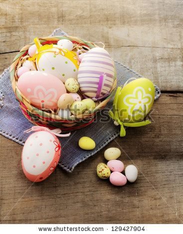 decorated easter eggs in a basket with chocolate eggs
