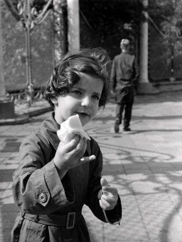 IJsjes. Een klein meisje loopt met een druipend ijsje (verpakt in een servet) in haar handje op straat.  Plaats en datum onbekend