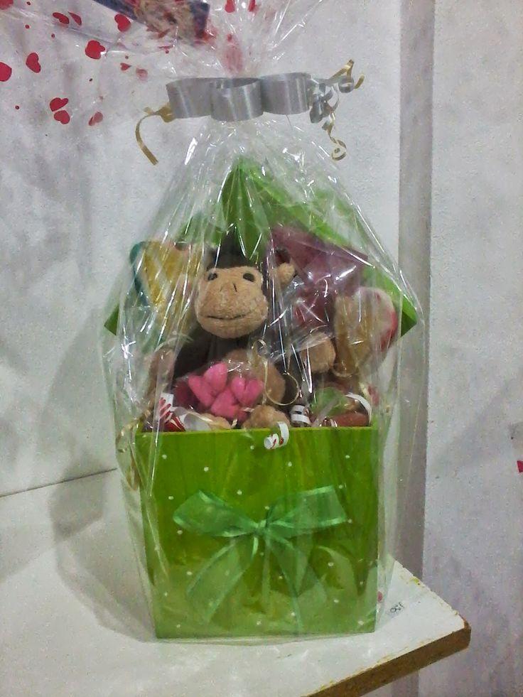 Caja de madera acompañada de golosinas y de muñeco de peluche.