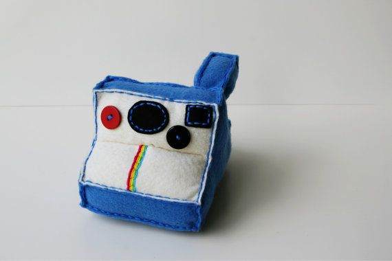 A *NEW* hand sewn felt Polaroid Plushy. Composed of Blue and Cream felt. 2 sewn on control buttons along with the rainbow trade mark; of the