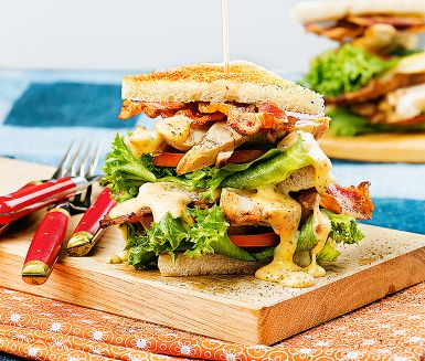 Club sandwich är en matig macka med kyckling, bacon, sallad och tomat som klassiska ingredienser. En god majonnäs till är ett måste – här smaksatt med sweet chilisås, som även ingår i kycklingmarinaden. Varva mackorna strax före servering.