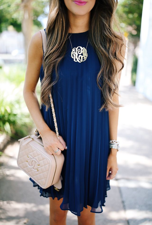 navy pleated dress, large monogram necklace