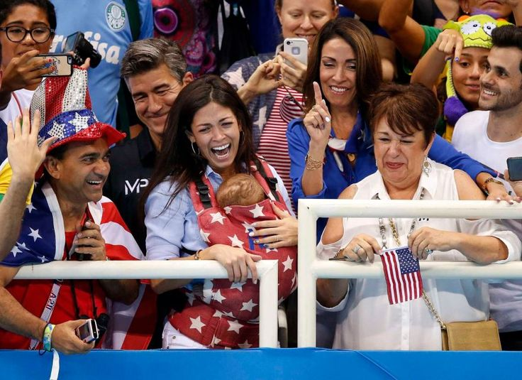 Nicole Johnson, center, wife of Michael Phelps of USA, their son Boomer and Michael's mother Deborah, right, talk to Michael Phelps (not pictured) during his lap of honor after the medal ceremony for the men's 4x100-meter freestyle relay final race of the Rio 2016 Olympic Games swimming events at Olympic Aquatics Stadium at the Olympic Park in Rio de Janeiro, Brazil on Aug. 7, 2016.