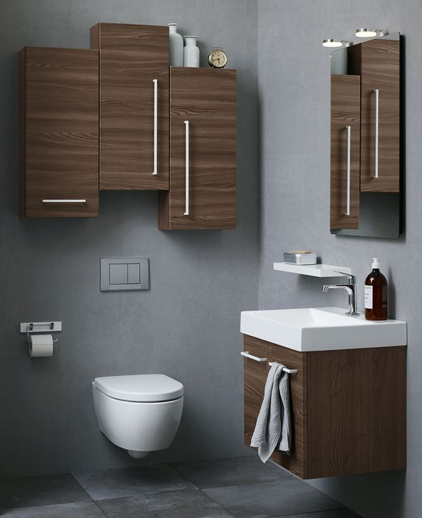 Mix heights and handles on cabinets to create an asymmetrical effect to give your bathroom character. Warm wooden finish in combination with cool white handles.