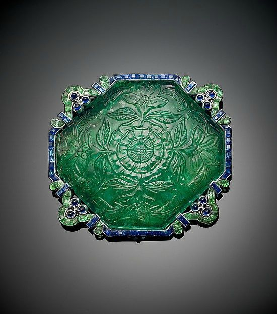 A brooch featuring a carved emerald bordered by calibré-cut emerald and sapphire…