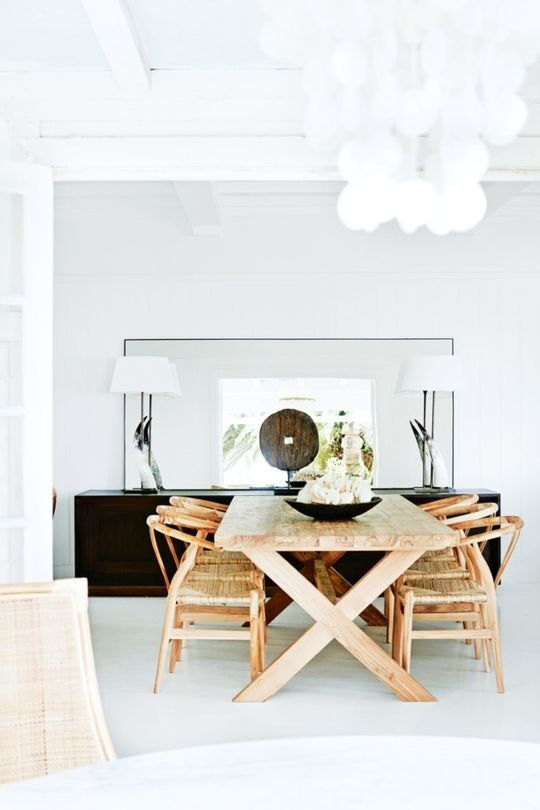 Bright and beachy dining space with wishbone chairs and a shell chandelier