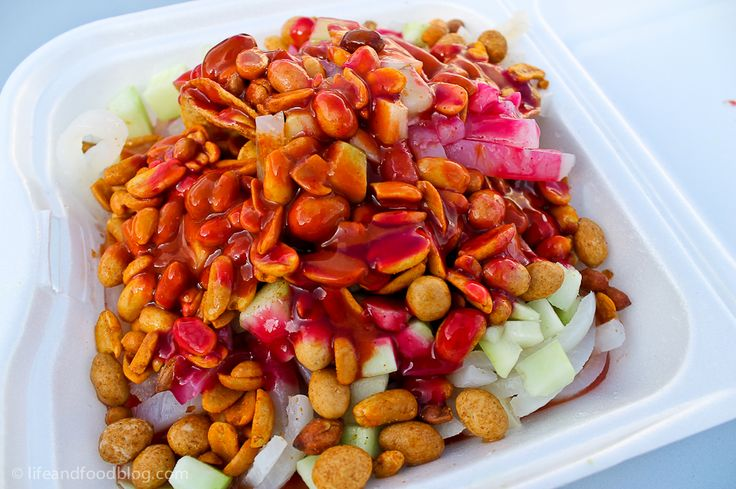 Tostilocos. Think Salsa Verde Tostitos topped with pickled pig skin, chile, chamoy, clamato, lime juice, cucumber, jicama, tamarindo candies, and japanese peanuts.