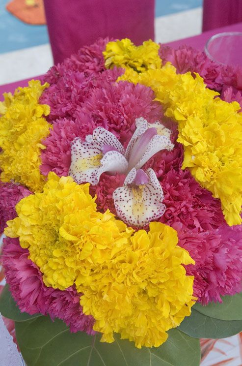 Tightly packed pink and yellow carnations surround pink speckled orchids.