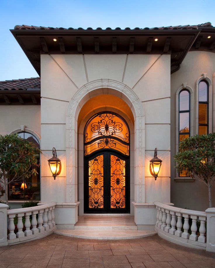 Rustic stonework welcomes you up the steps of this magnificent Mediterranean home where a warm glow shines through lovely, ornate glass and metalwork doors. With stucco exterior and a tiled roof, this home typifies its classic style with a modern flourish.