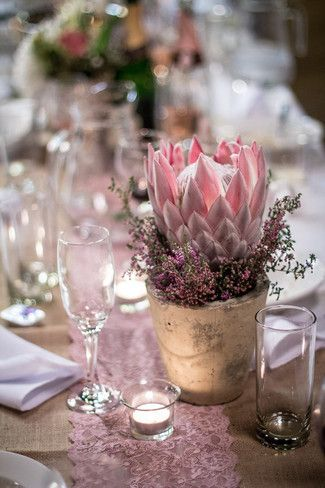 Rustic floral decor displayed upon a pink lace table runner.