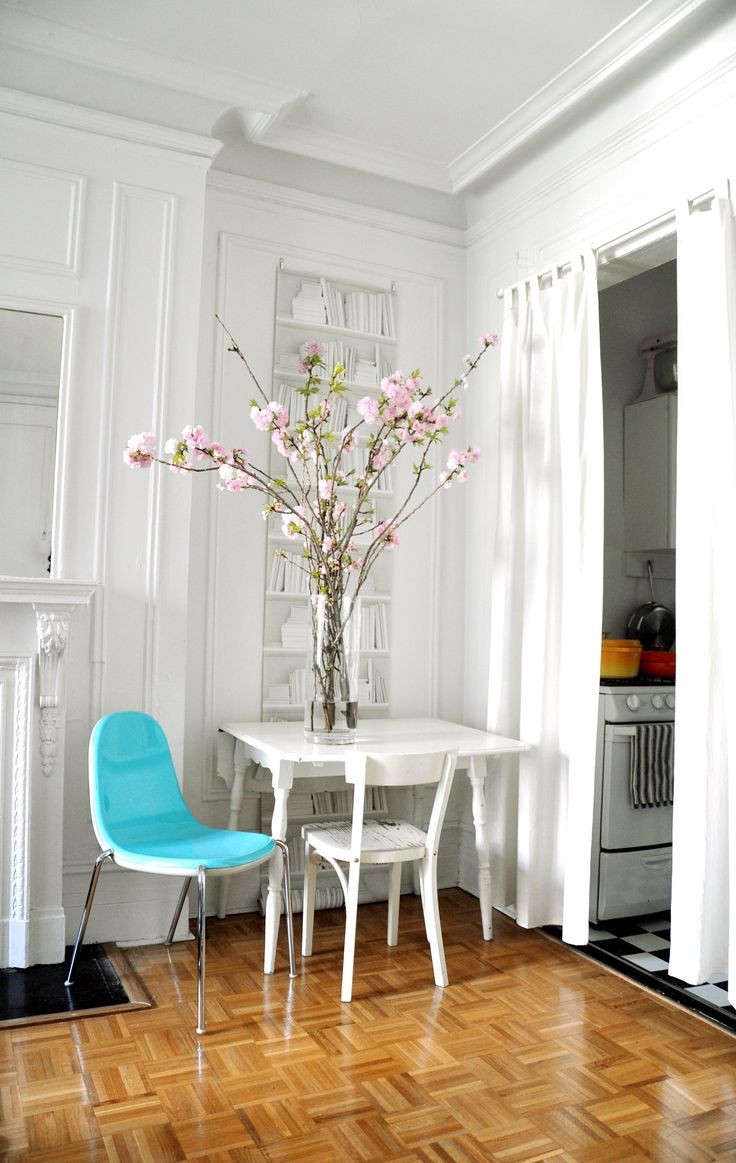 Small white apartment with parquet floor, curtained doorway to kitchen