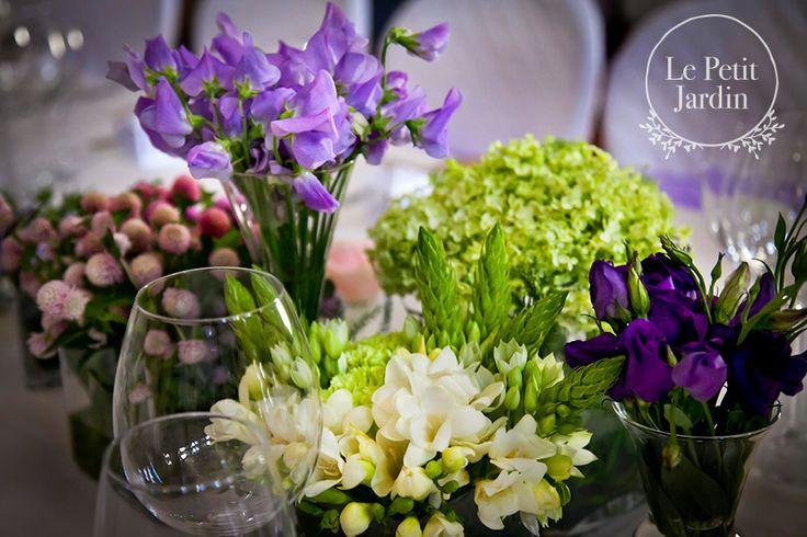 Dettaglio - tavola decorata con piccoli vasetti di differenti altezze, ognungo con un diverso tipo di fiore.