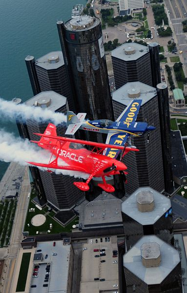 Mike Goulian in the Goodyear Extra 330 and Sean D. Tucker in the Team Oracle Challenger 3 plane fly over downtown Detroit. Goulian and Tucker will be performing at the 2013 Thunder Over Michigan air show at Willow Run Airport.