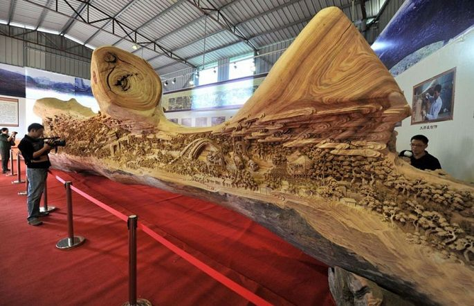"""Artist Zheng Chunhui is the master of wood.  """"Along The River During The Quinming Festival"""" is carved into a 12-foot-long driftwood tree."""